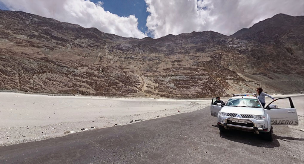 2 km dead straight road running through the sands in Nubra Valley under a vivid blue sky surrounded by mountains